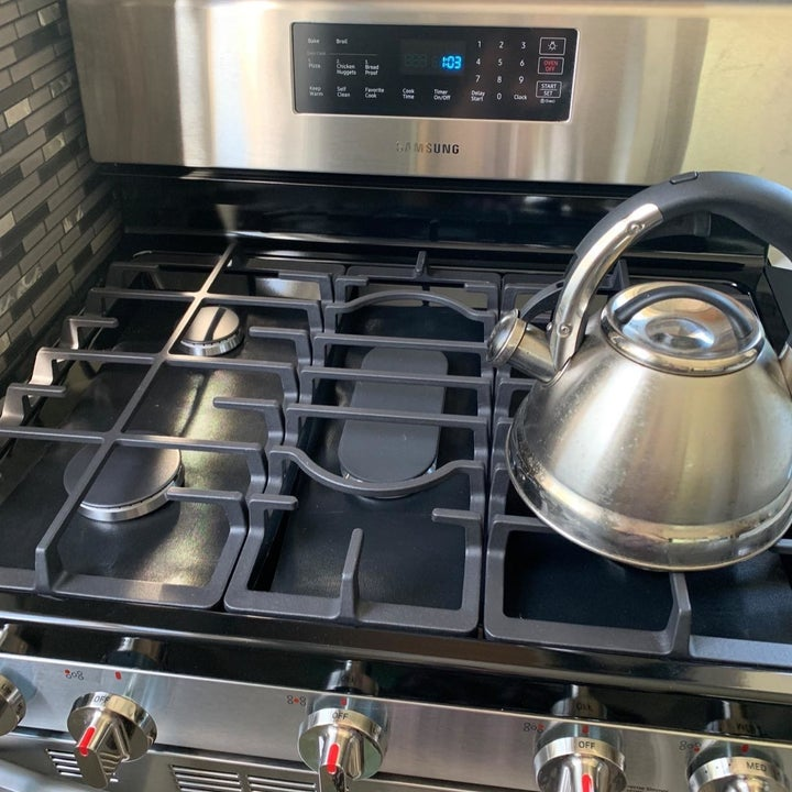 Reviewer showing the liners on their stove top
