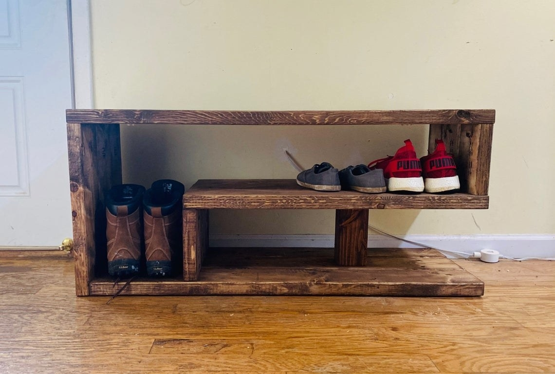 Asymmetrical, rustic bench with negative space open for shoes