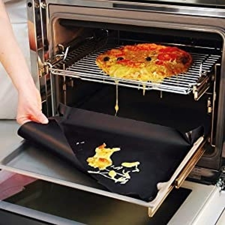 Liner being used to catch pizza melting spill in an oven