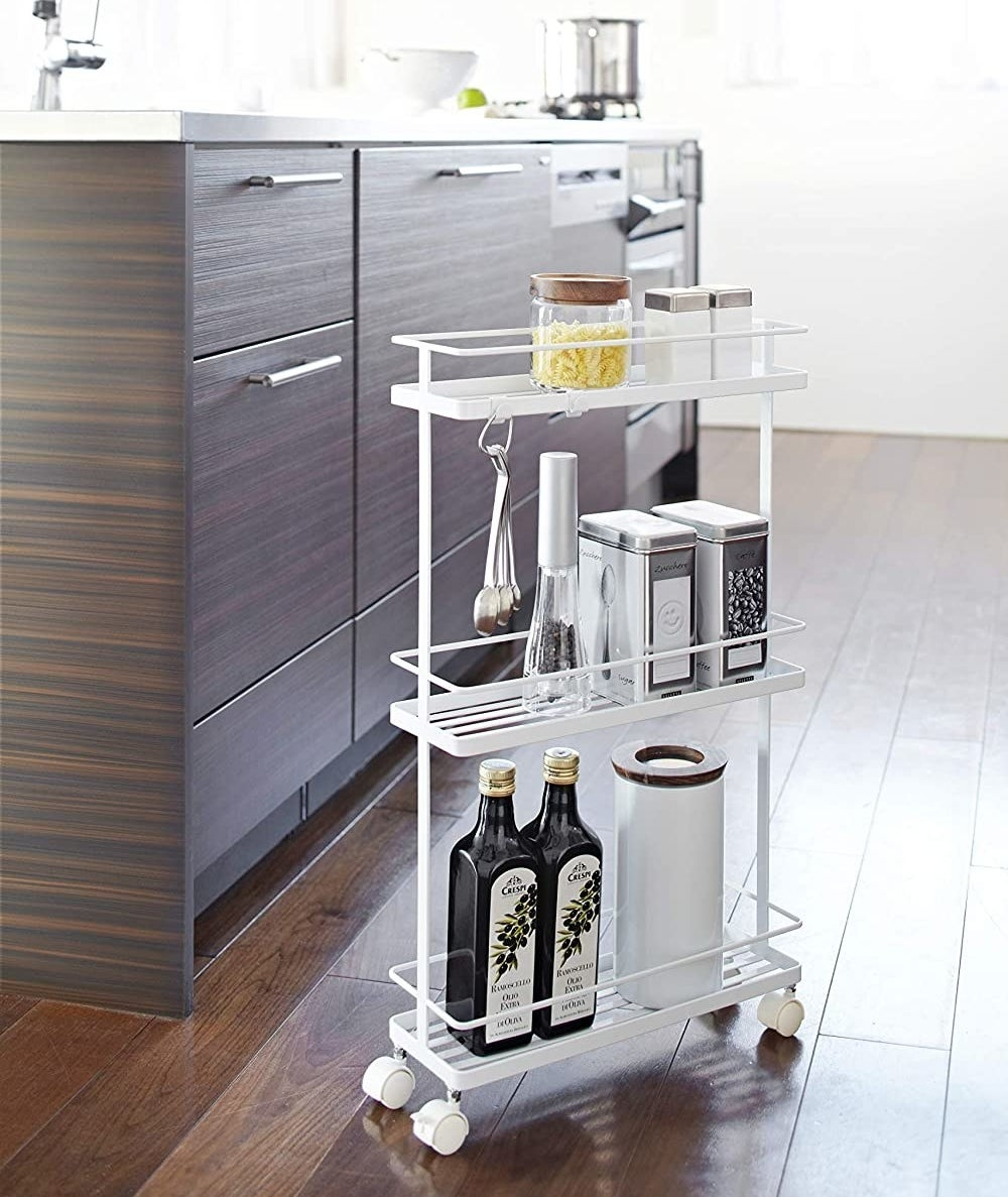 A slim storage cart that has three tiers and wheels The tiers are filled with food storage containers and canisters
