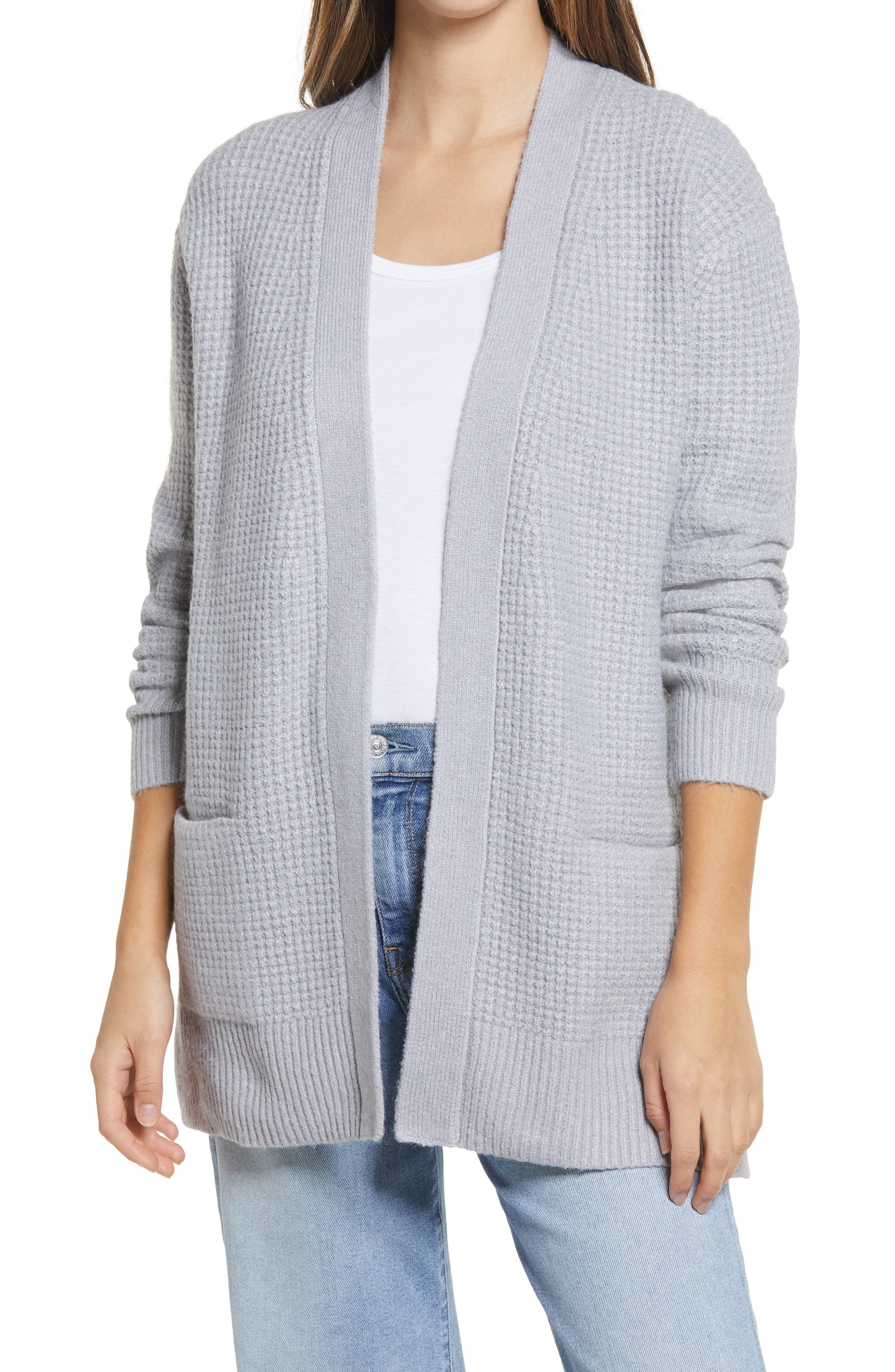 model wearing a grey waffle knit sweater over a white shirt and jeans