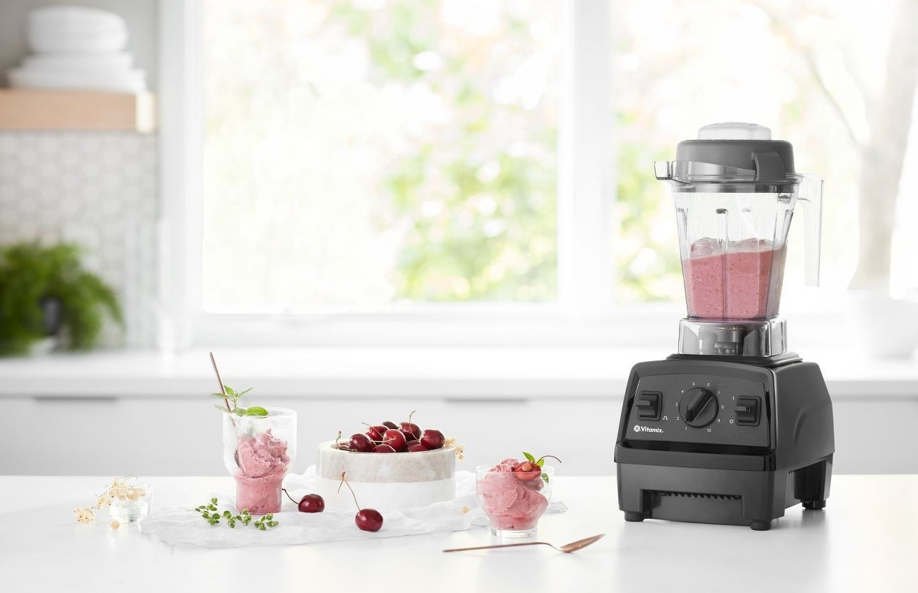 The blender on a countertop with fruits and ice cream