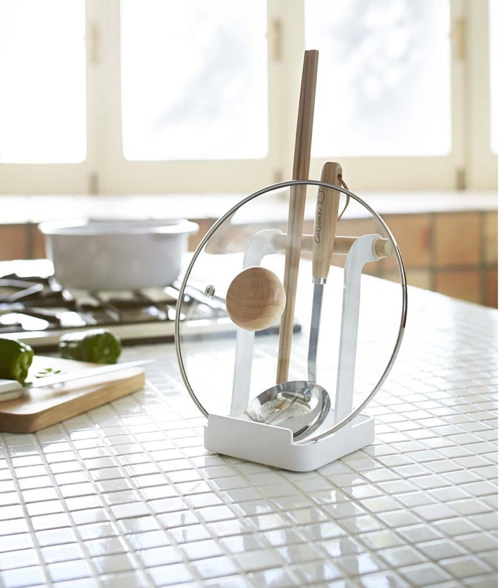 A small stand with a pot lid and ladle resting on it