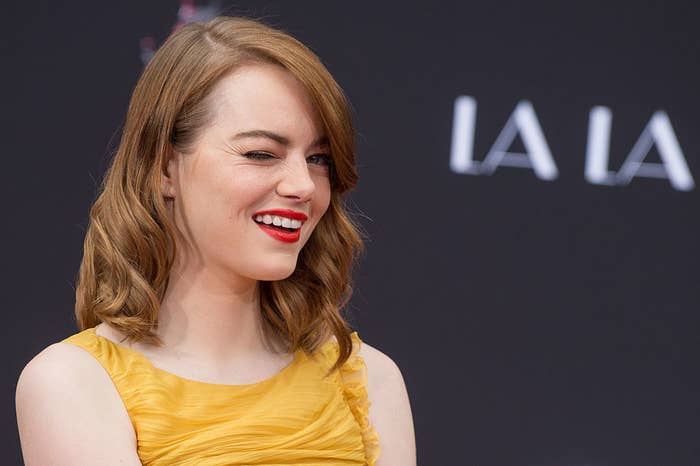 "Emma Stone winking and smiling at ""Ryan Gosling and Emma Stone hand and footprint ceremony'"" at  the TCL Chinese Theatre IMAX in December 2016"