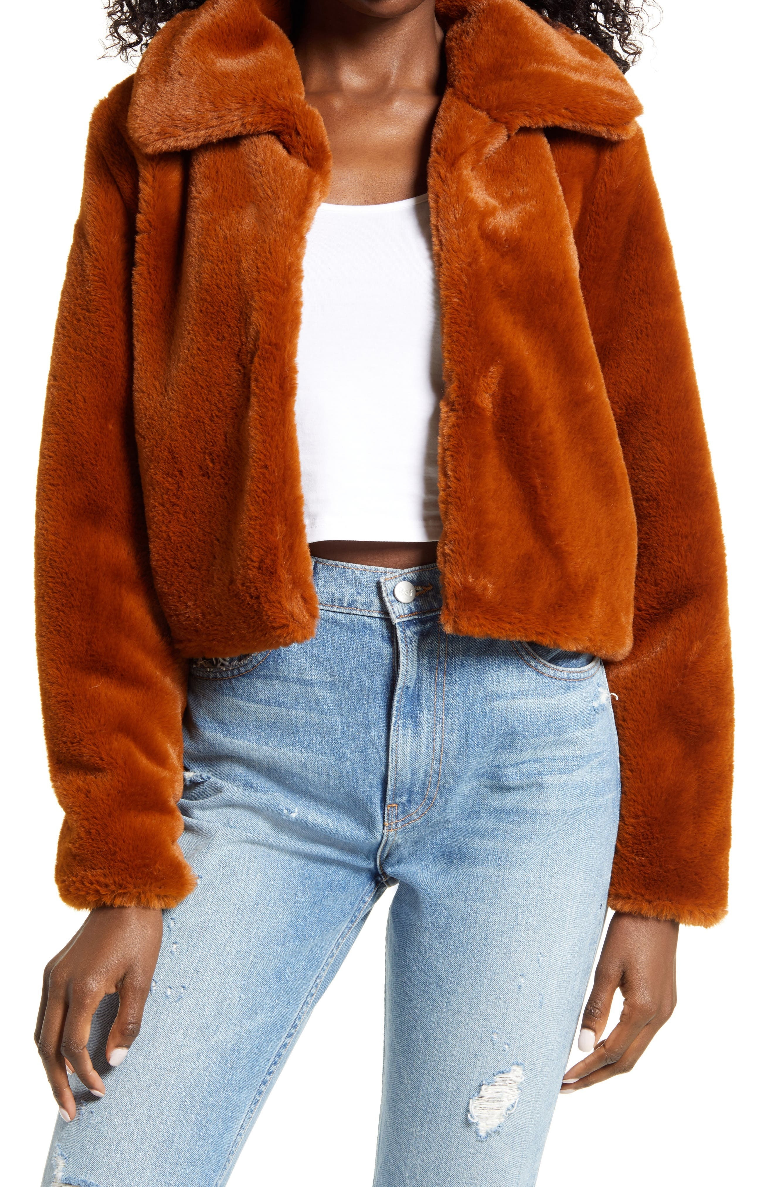model wearing an cropped orange faux fur jacket over a white shirt and blue jeans