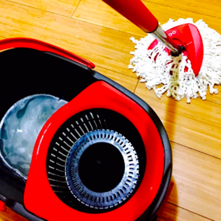 Reviewer showing small mop cleaning floor and soapy water in bucket