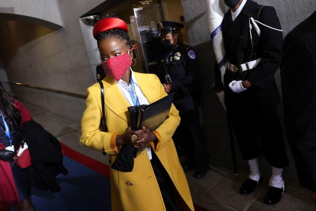 Amanda Gorman walking to the stage at the 2021 presidential inauguration, she is wearing a long yellow jacket and red face mask