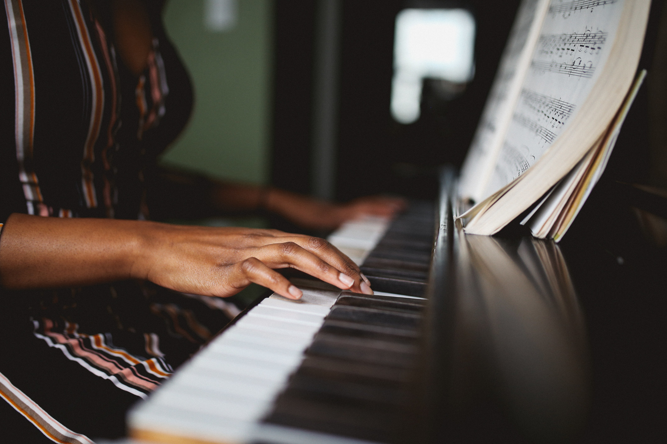 An up-close shot of someone's hands playing piano