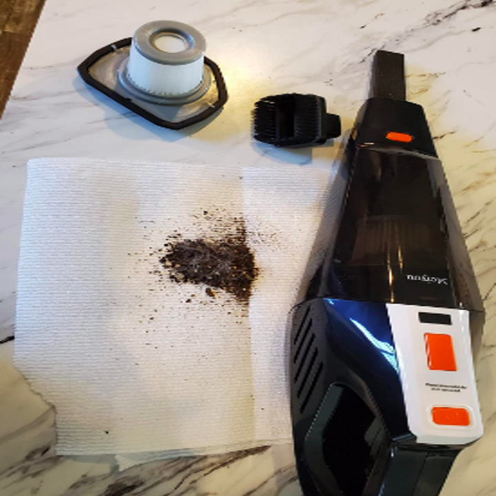 Reviewer with small vacuum beside two different heads, with a paper towel covered in the dust and grime vacuumed up in the car