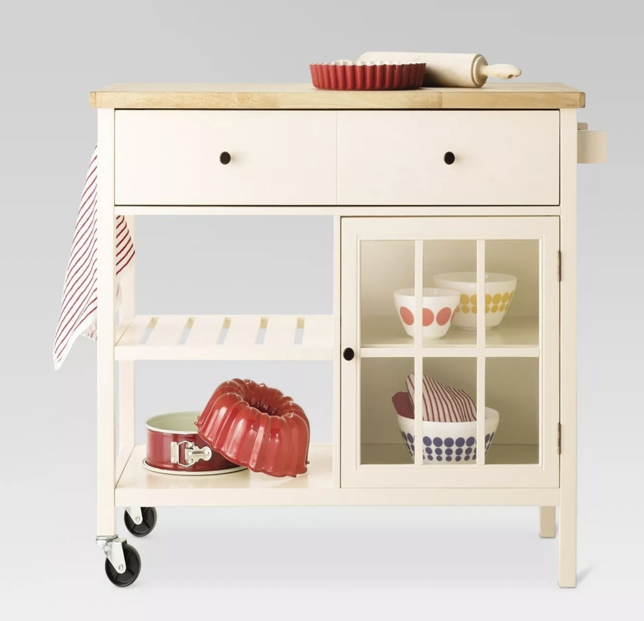 a cream kitchen cart with two wheels and two legs, with two drawers, one glass door with two shelves inside, and two shelves unprotected by a door