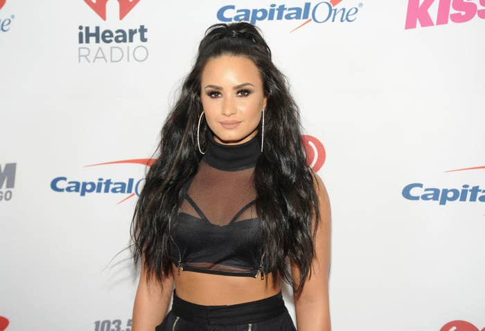Demi with her hair half up and half down and sporting extra-large hoop earrings