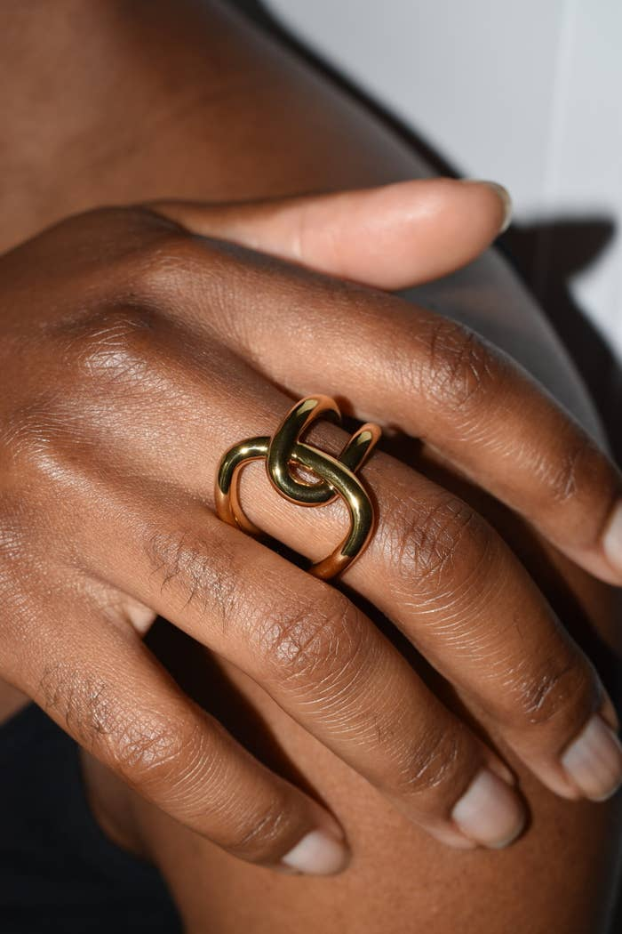 close-up of a model wearing a ring that has two gold loops that are interlocked with each other