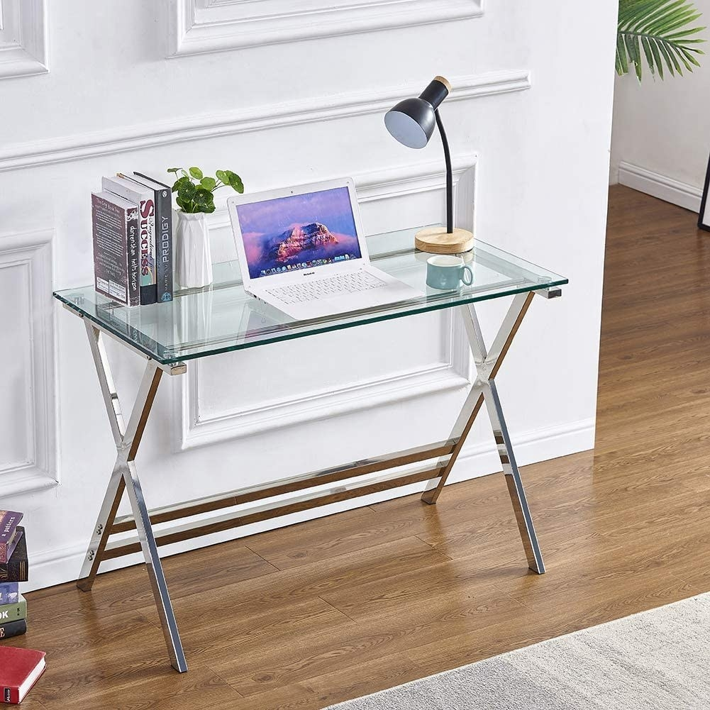 the glass top writing desk in a living space with a laptop and several books on its surface