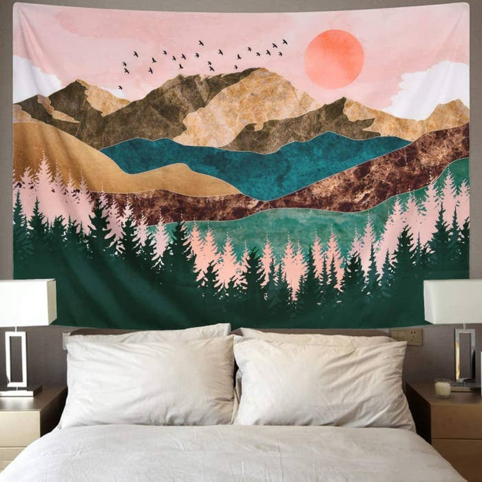 The vividly colored tapestry, featuring trees, mountains, birds, and more, hanging above a bed
