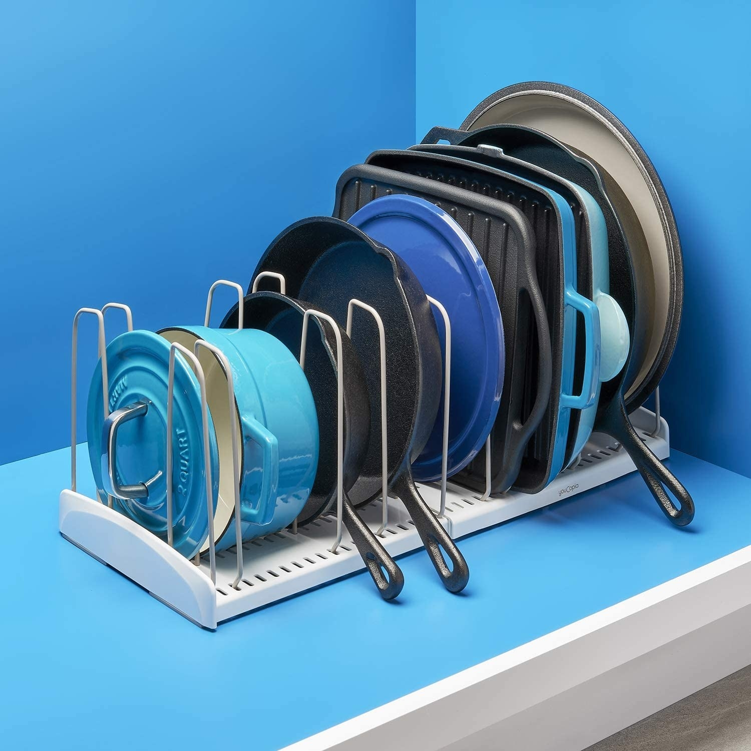 white expandable cookware rack with neatly organized pots and pans