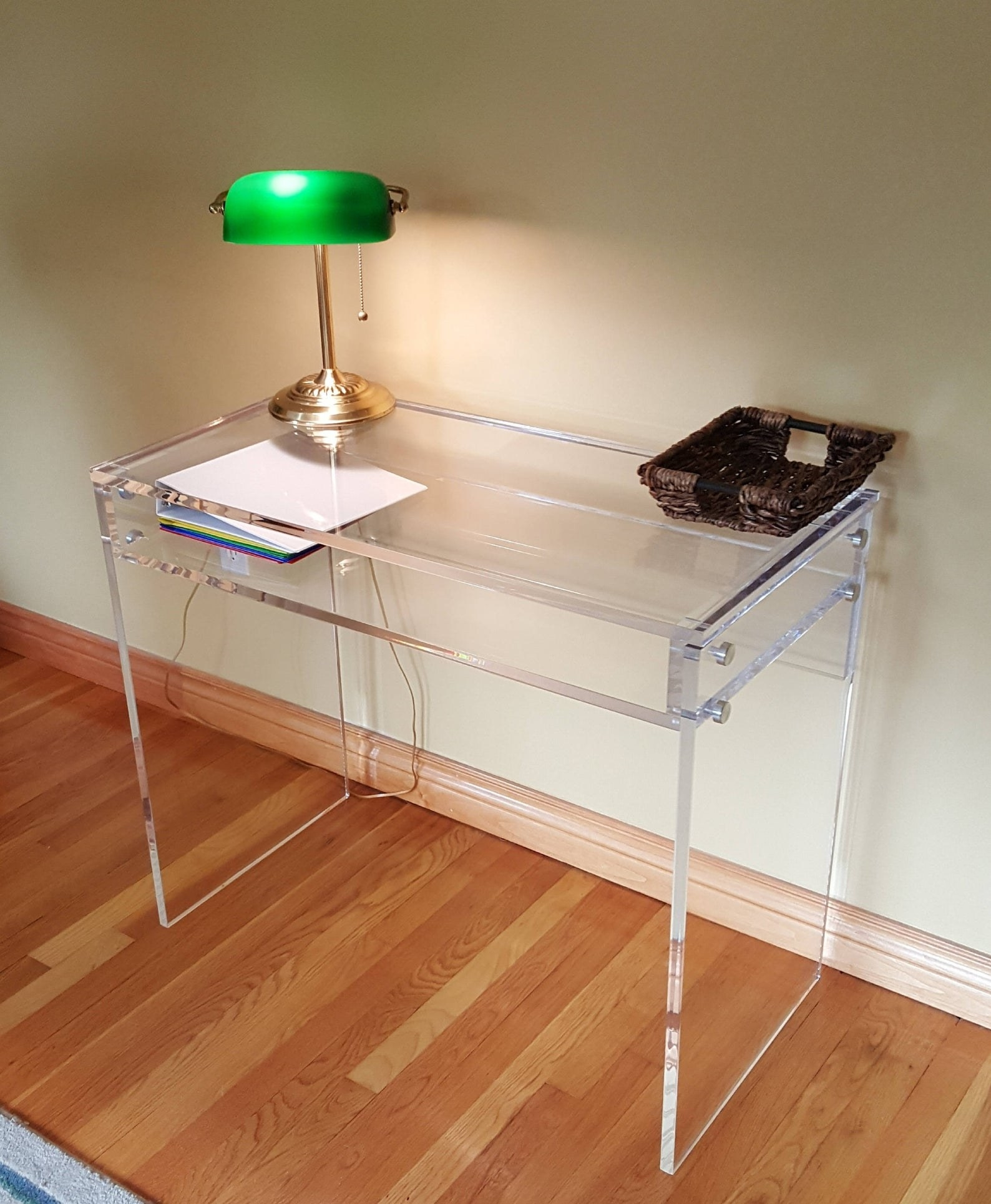 a custom acrylic desk with an antique lamp on top of it