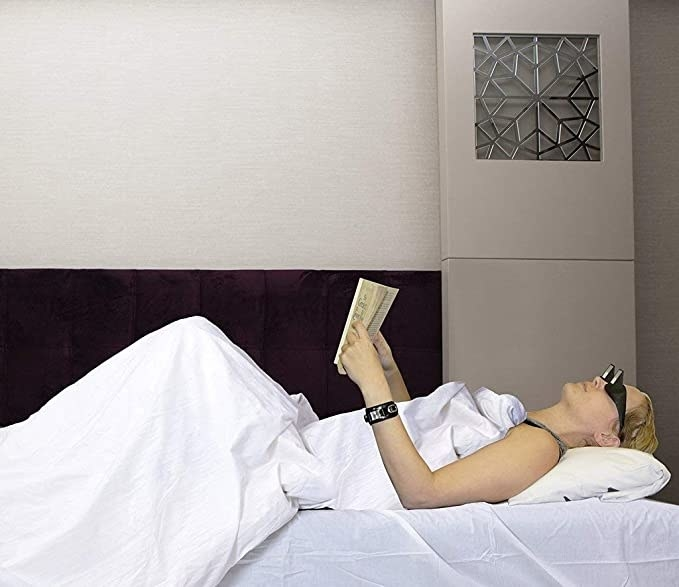 Woman reading a book in bed wearing the lazy glasses.