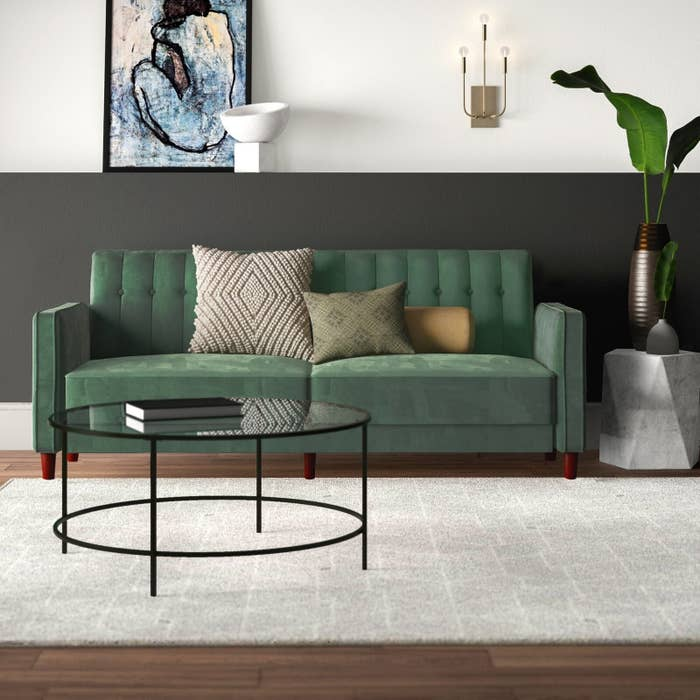 The couch in green, which has two wide seat cushions and small wooden legs