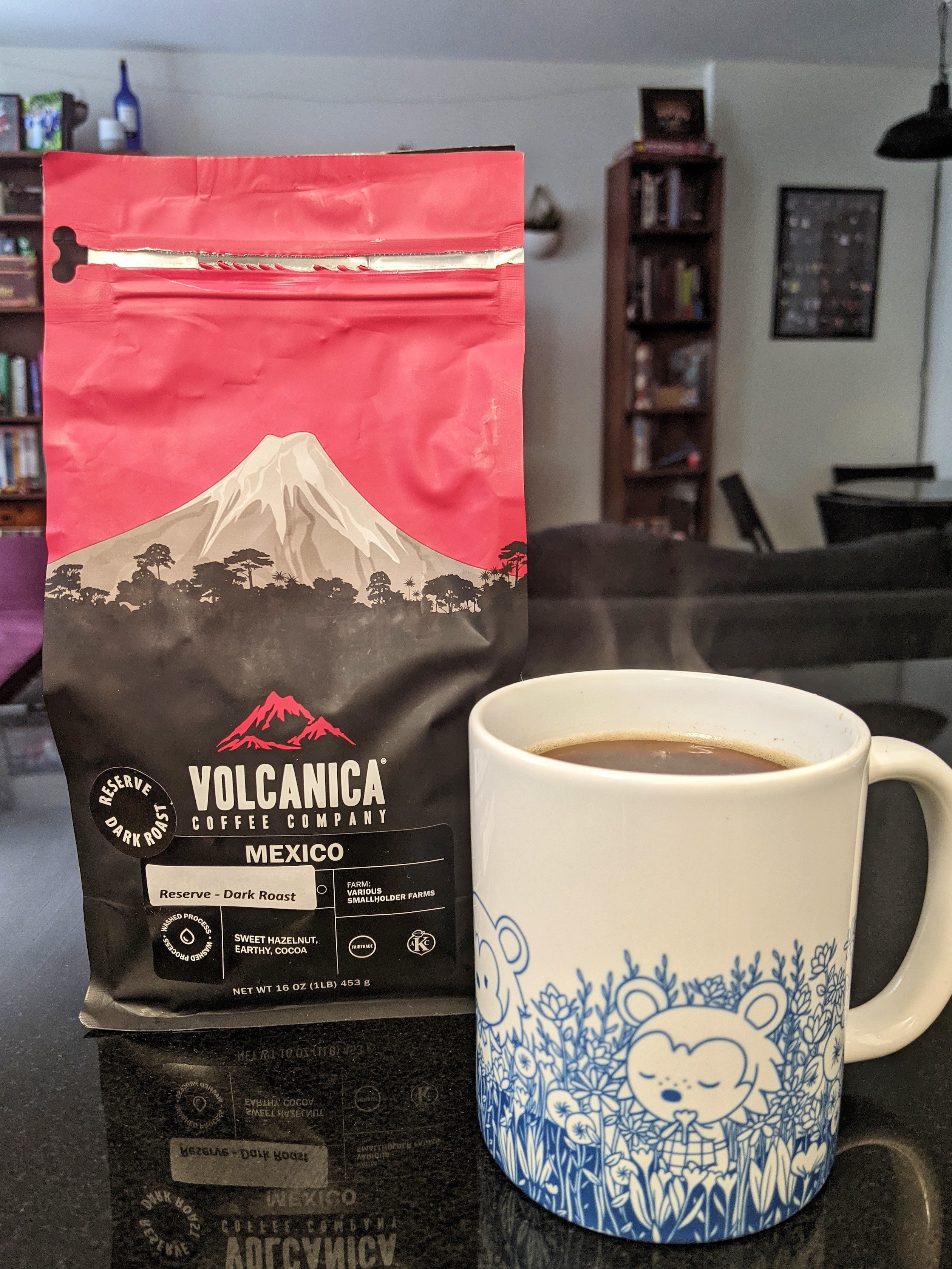 A bag of Mexican Reserve Dark Roast coffee beans next to a mug filled with coffee