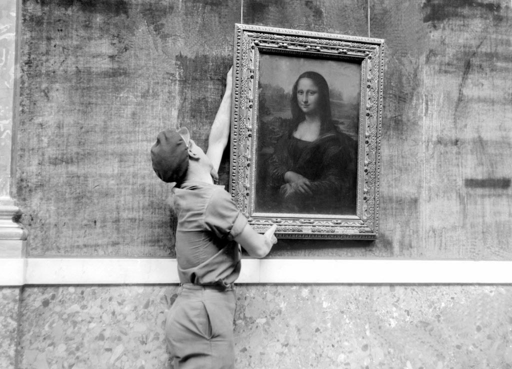 Person hanging the Mona Lisa painting on a wall