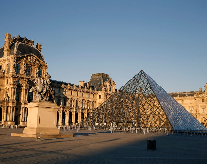 The beautiful, old Louvre Museum building and a glass pyramid in the courtyard