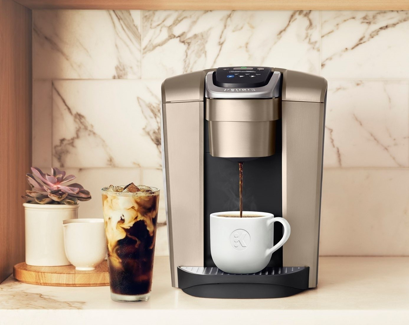 The coffeemaker in gold, shown on a countertop with hot and iced beverages