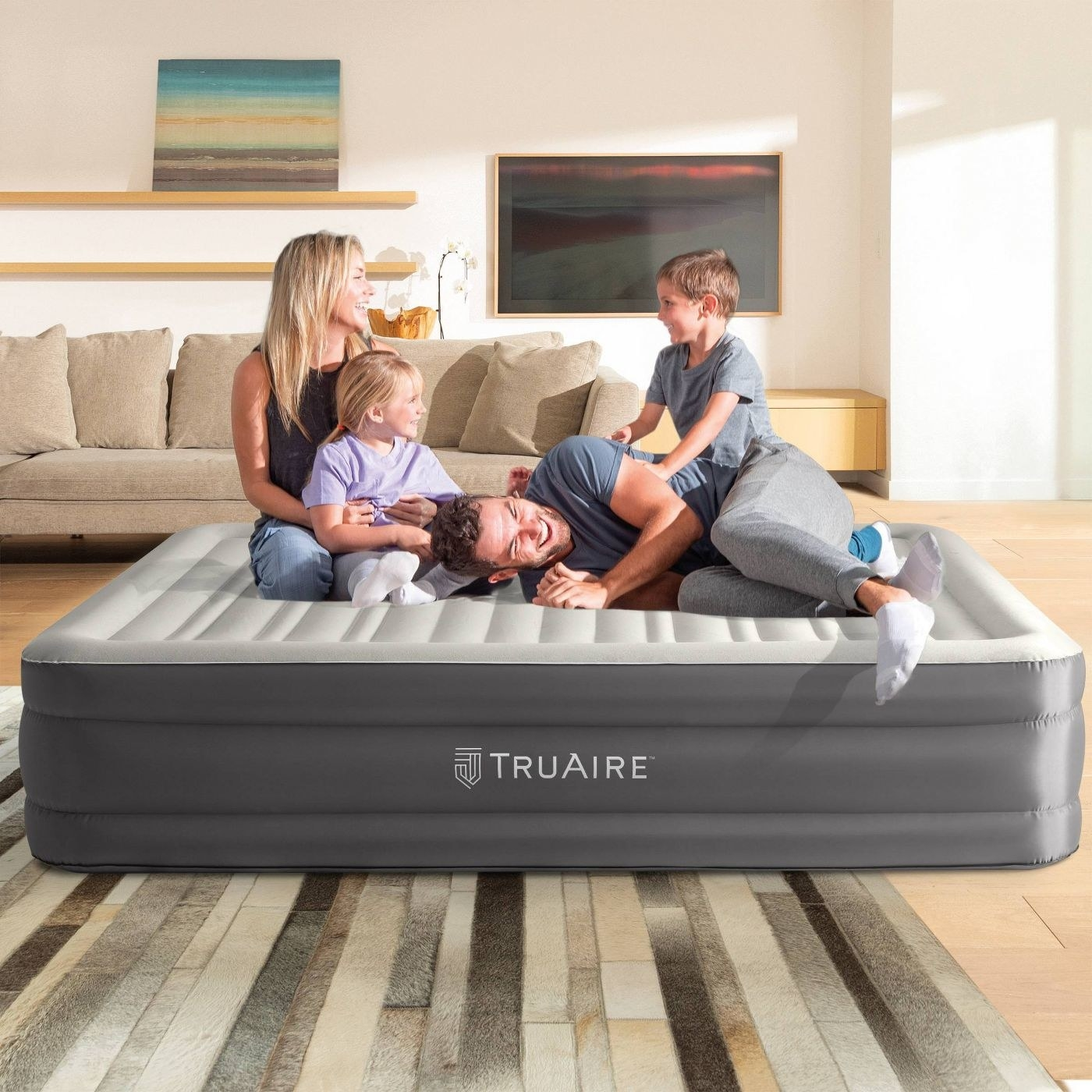 People resting on the air mattress in a living room