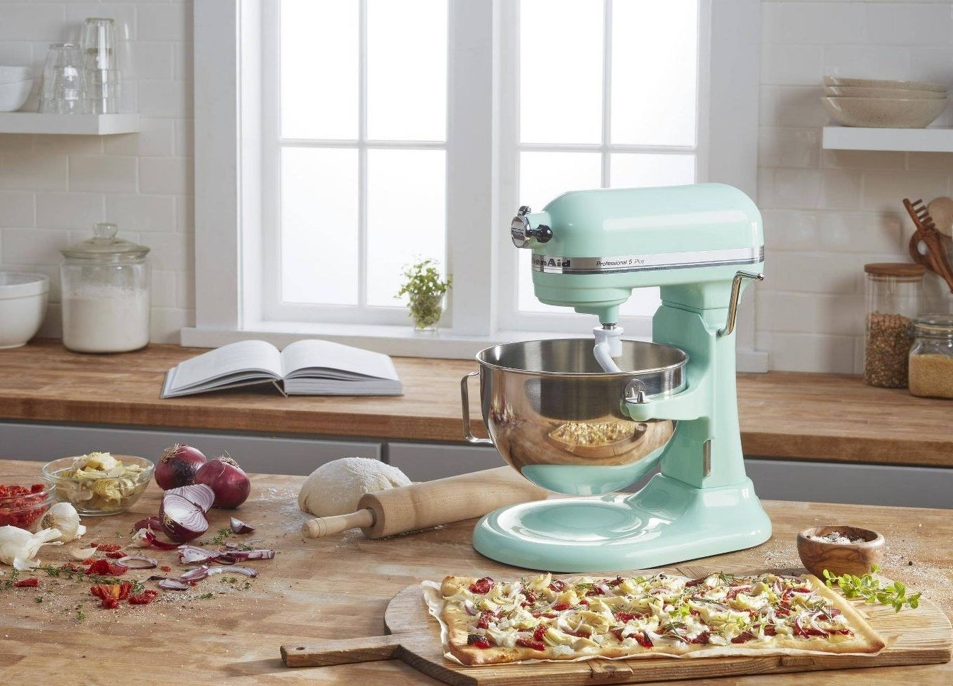 The mixer on a countertop with a pizza and ingredients