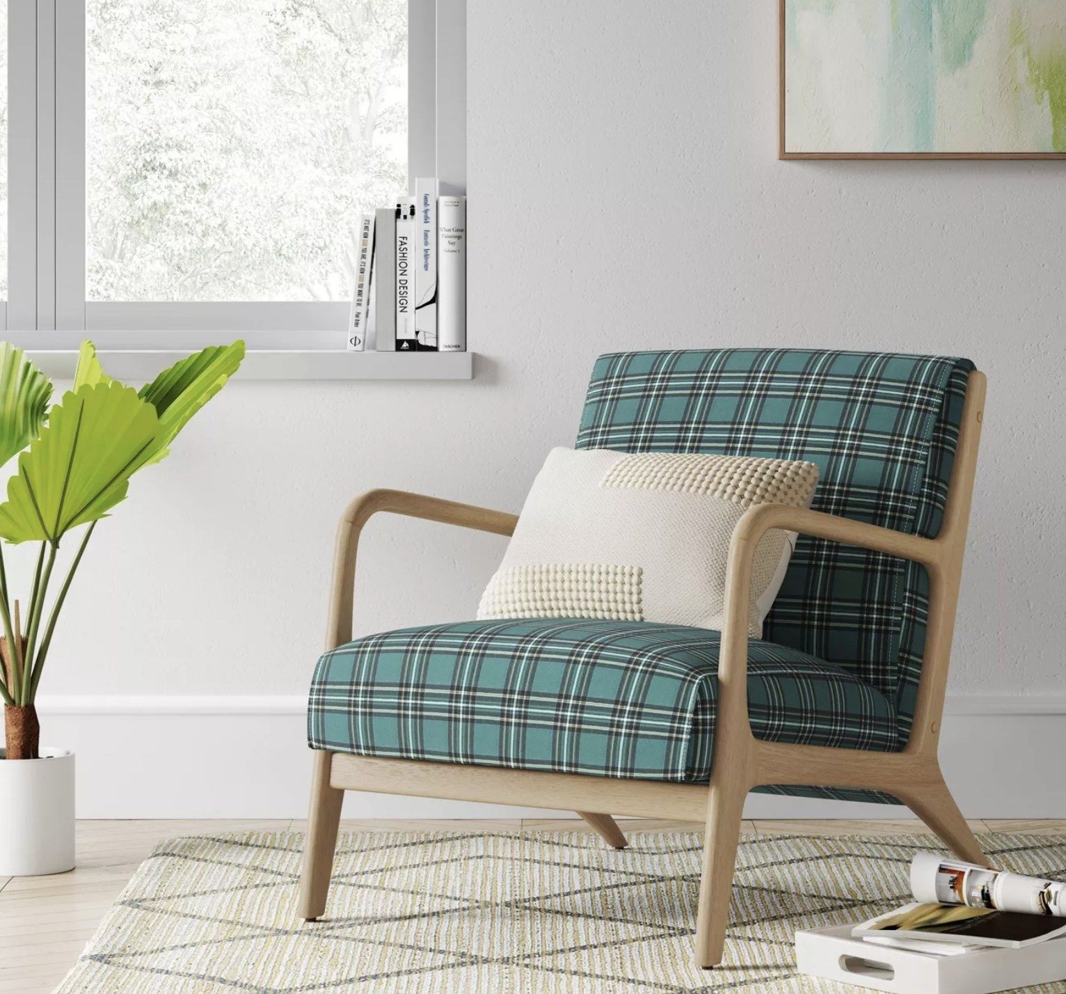 a green black and white plaid upholstered armchair with light wood arms and legs, sitting in a corner