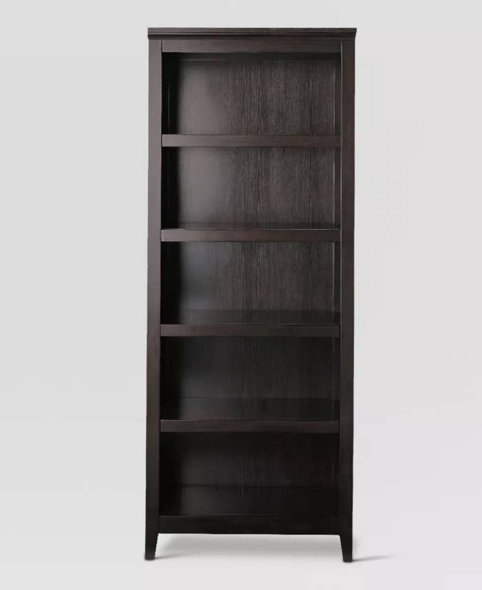 a tall brown bookshelf with five shelves