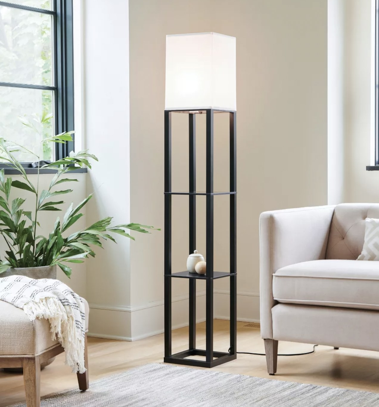 a floor lamp with a white cube lampshade and two black metal shelves