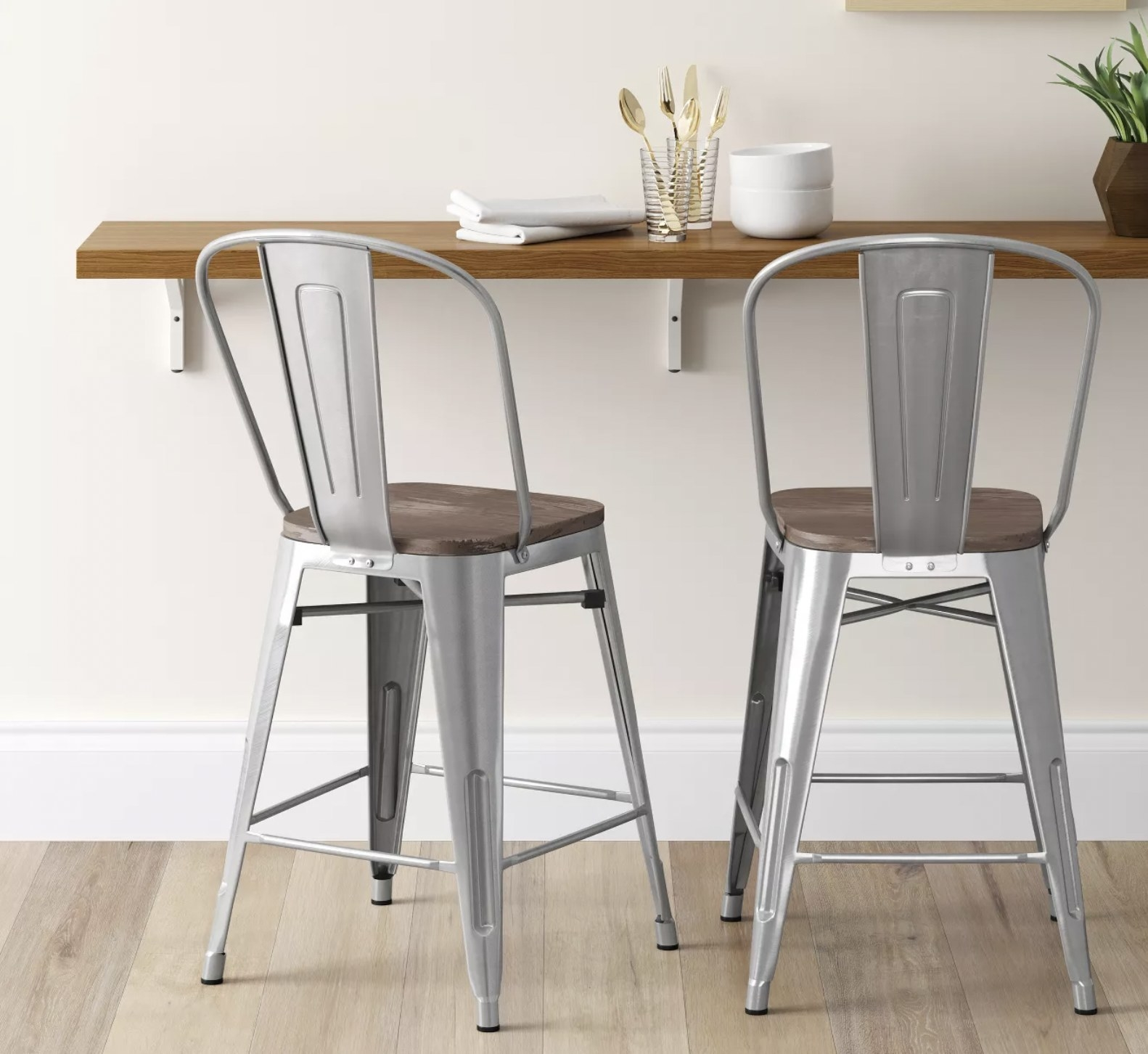 two silver metal bar stools with metal legs, a backrest, and a wooden seat, propped in front of a bar