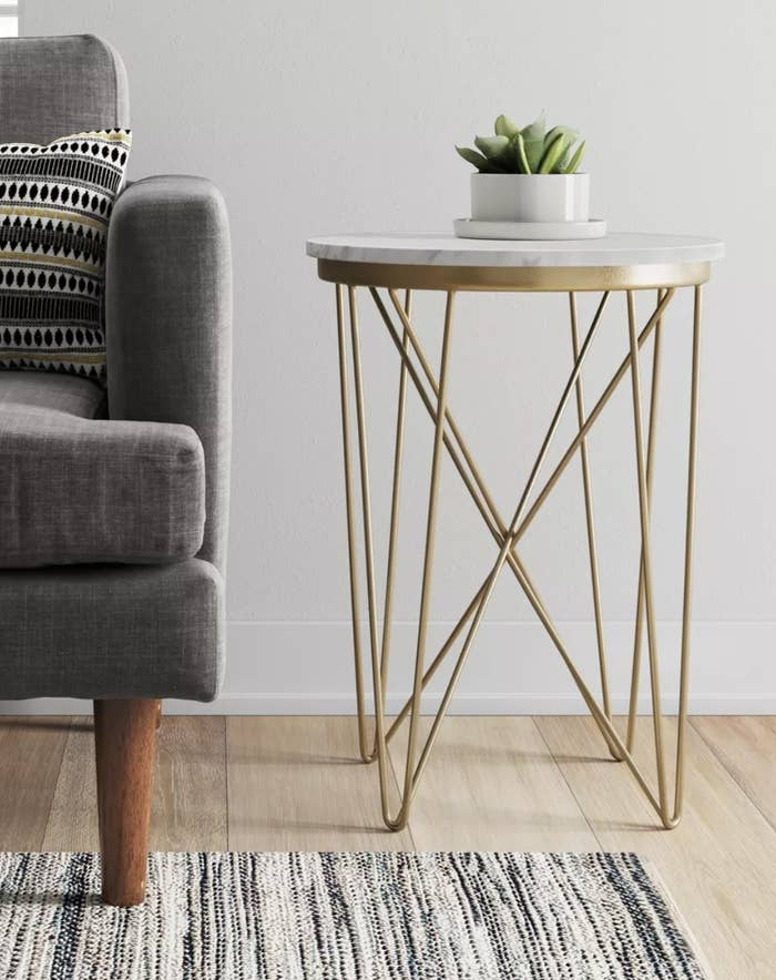 a marble top end table with brass legs next to a couch