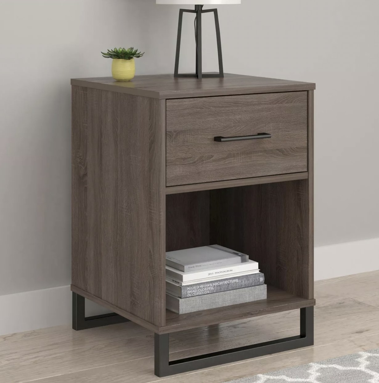 a grey-brown mixed-material nightstand with one drawer and one shelf