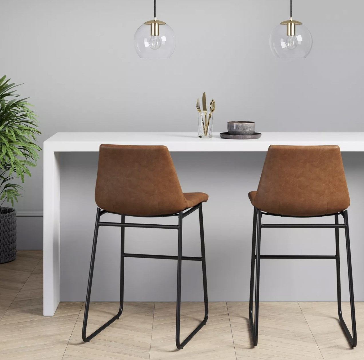 two faux brown leather bar stools with backs and black metal legs, at a counter