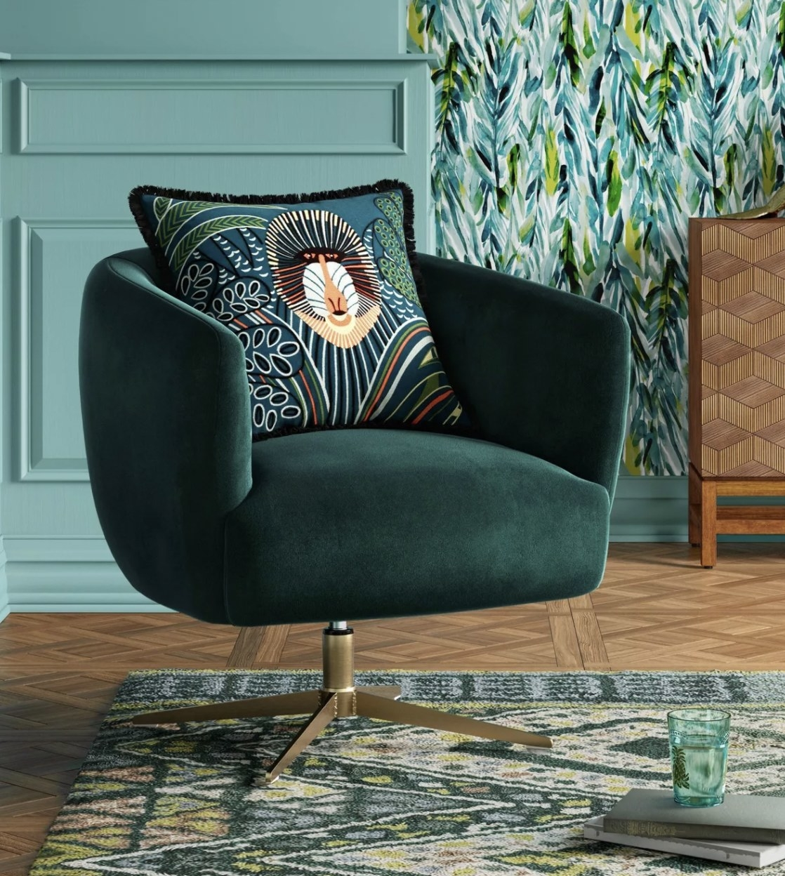 a green velvet armchair that swivels, with brass legs. The chair is sitting in a green room