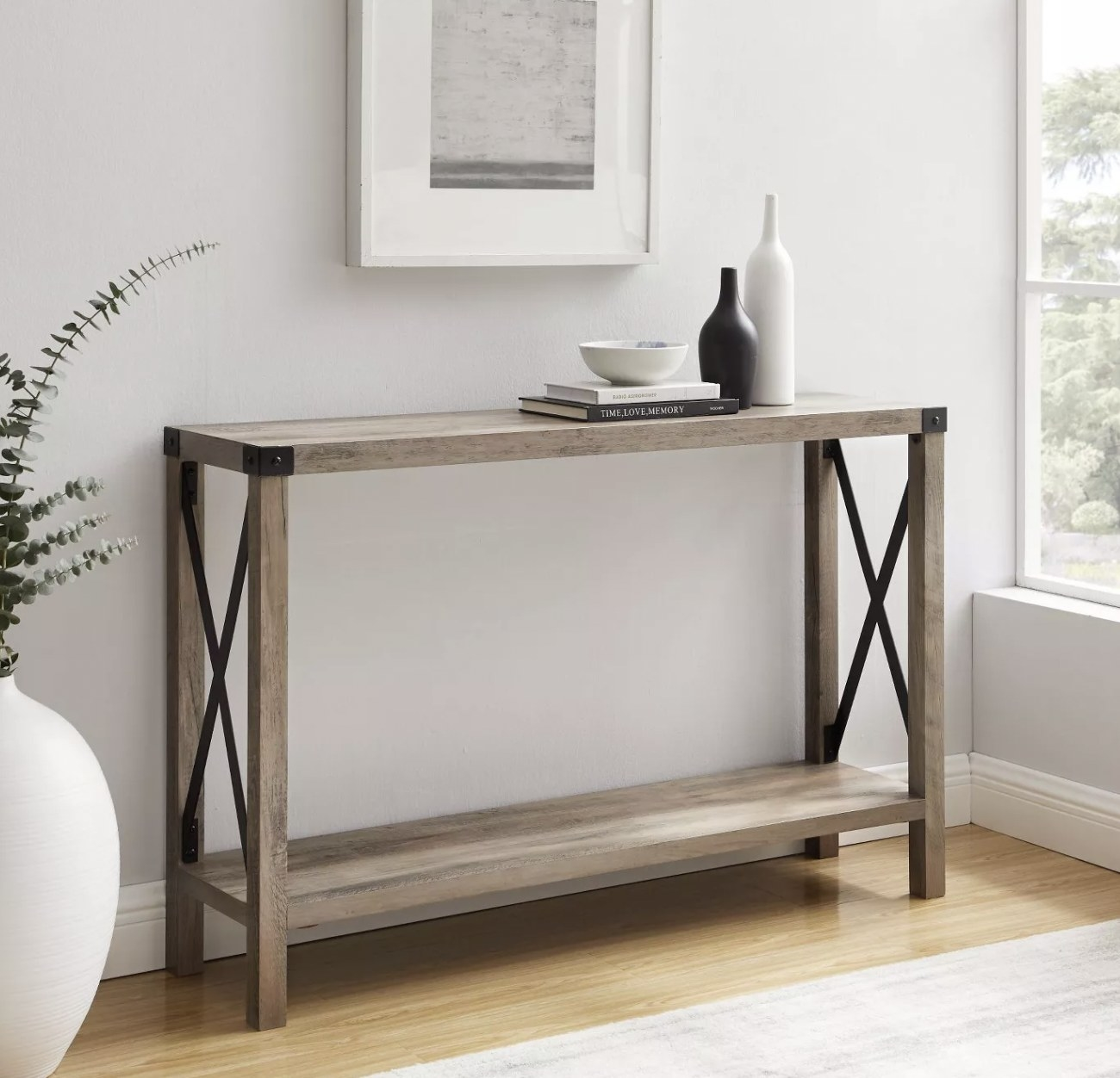 a grey-beige thin console table with black metal hardware, holding decor on its top shelf with an empty bottom shelf