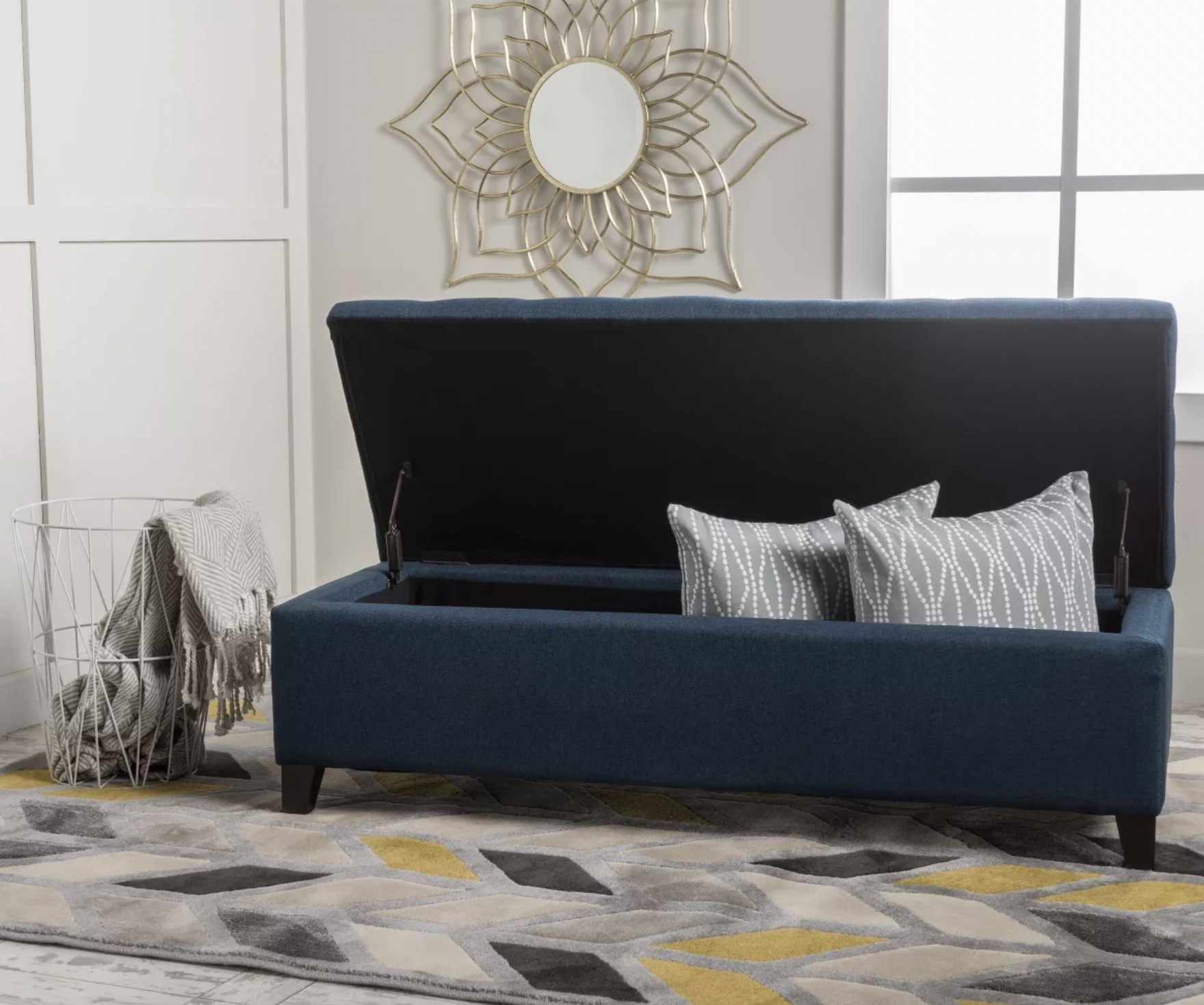 a navy blue ottoman with its top flipped open, revealing storage inside