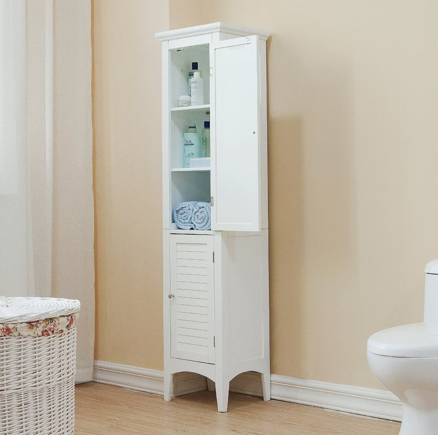 a white two-door shuttered linen cabinet with the top door open, revealing three shelves holding linens and toiletries