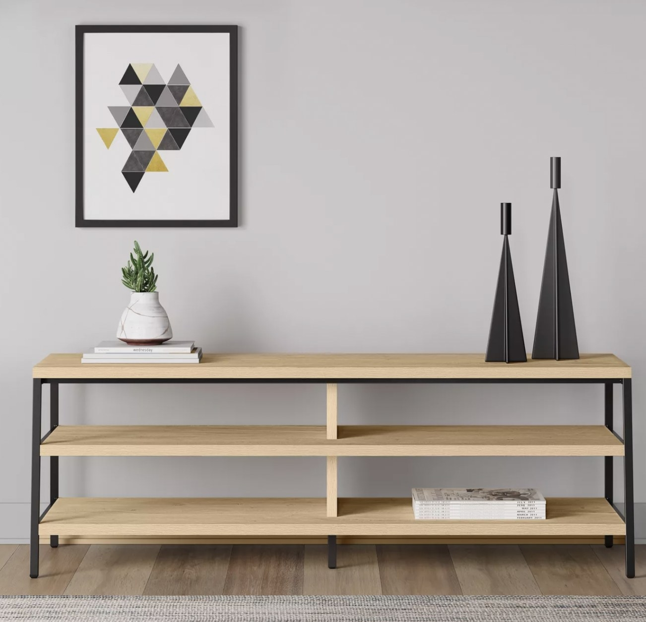 a light wood tv stand with four shelves, and one long shelf on top to hold a TV. This stand has black metal legs