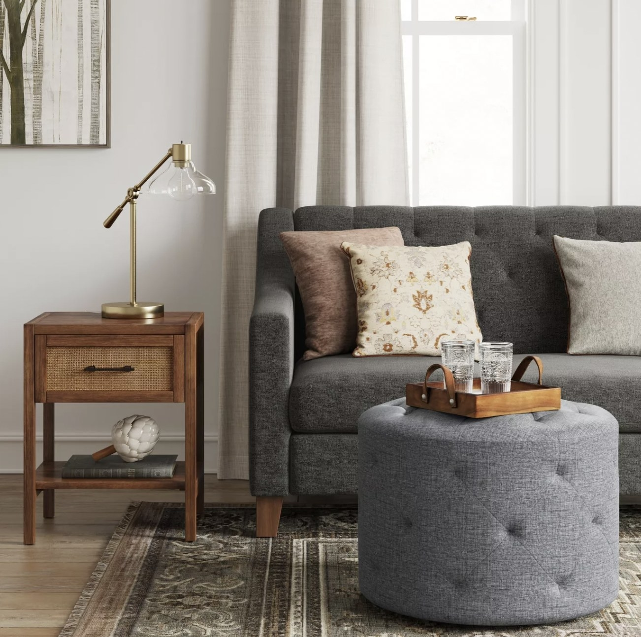 a round grey tufted ottoman in front of a couch, acting as a coffee table