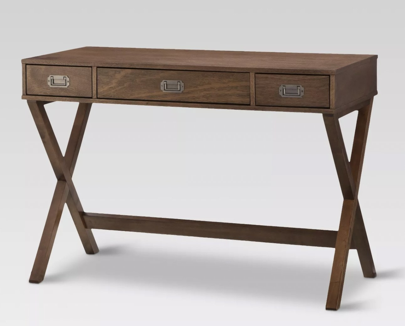 a brown wooden writing desk with three drawers