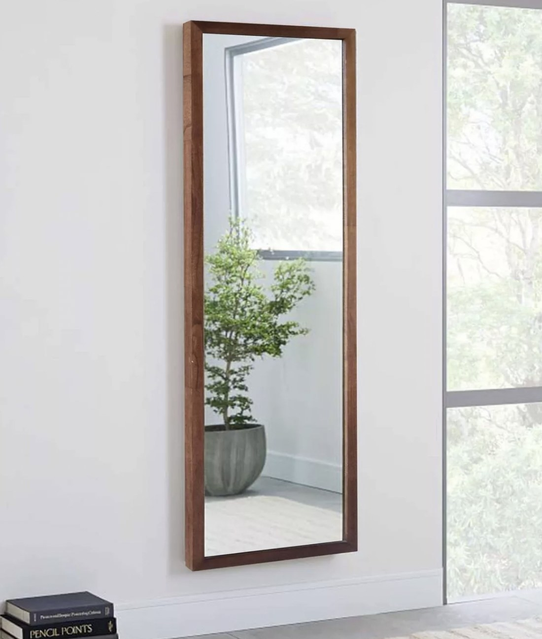 a fulll length mirror with a brown wooden frame hanging on a wall