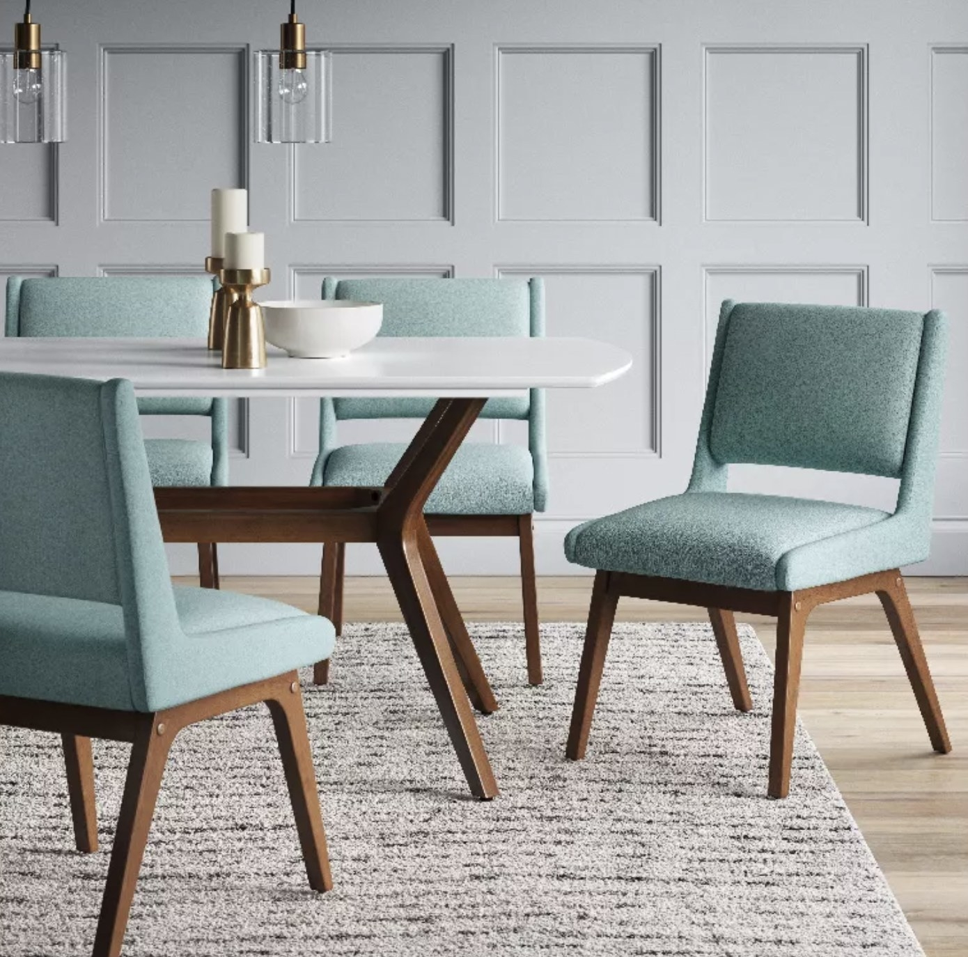 a teal upholstered dining chair with a backrest and tan wooden legs