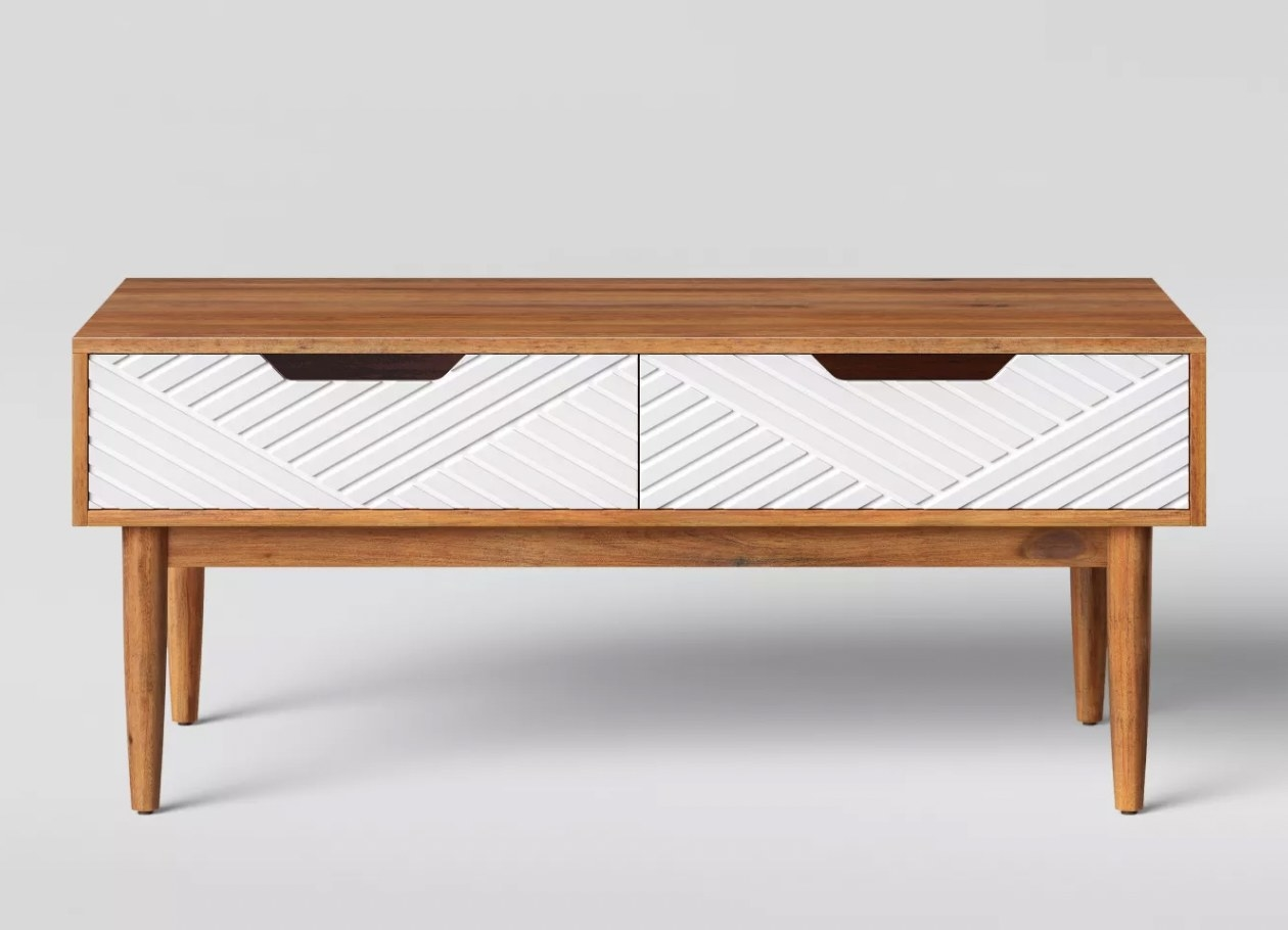 a tan wooden coffee table with two white drawers and four tan legs