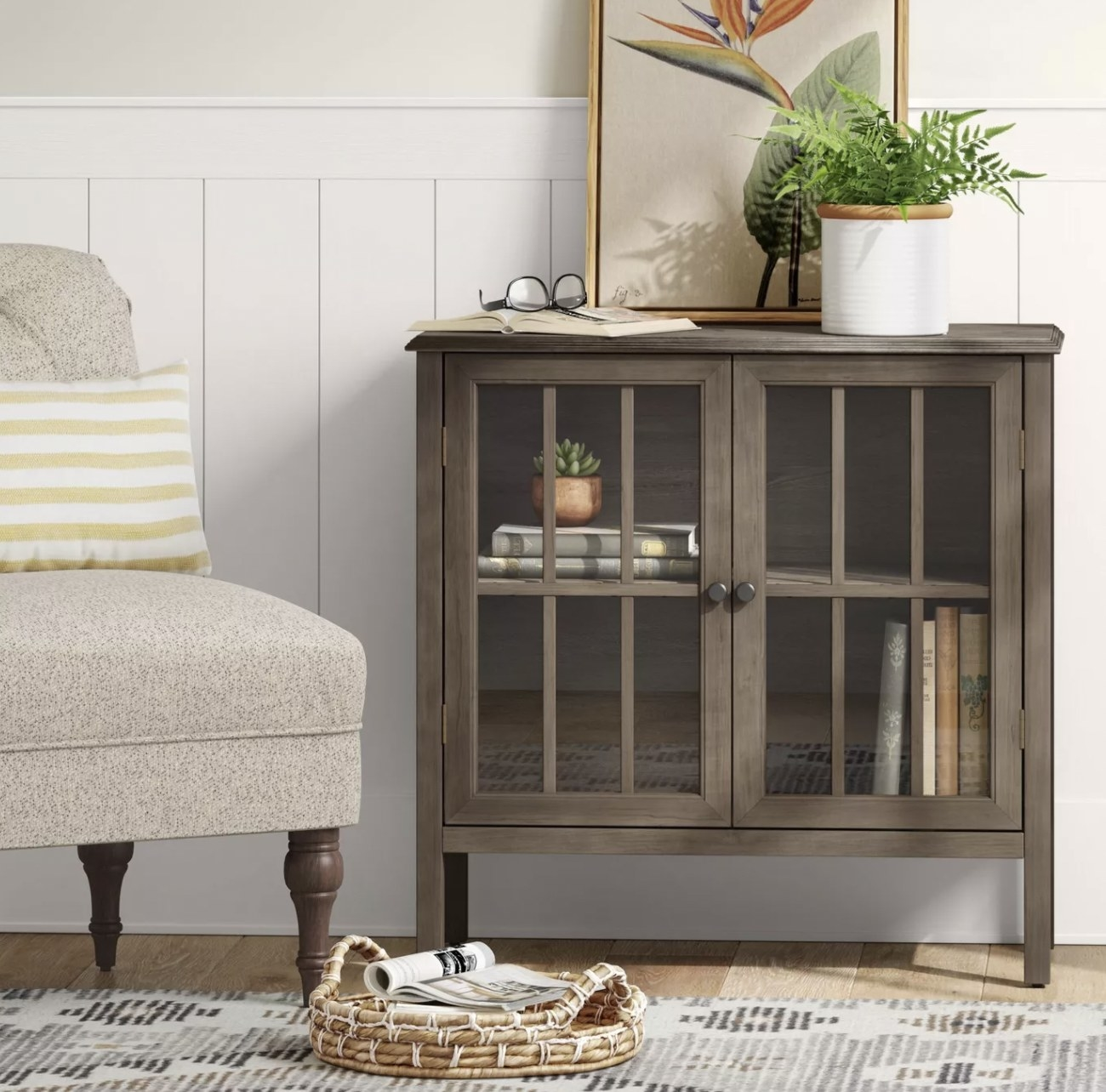 a brown accent cabinet with two shelves inside and glass doors