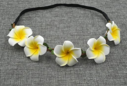 Small foam-like frangipanis roped together on a black headband