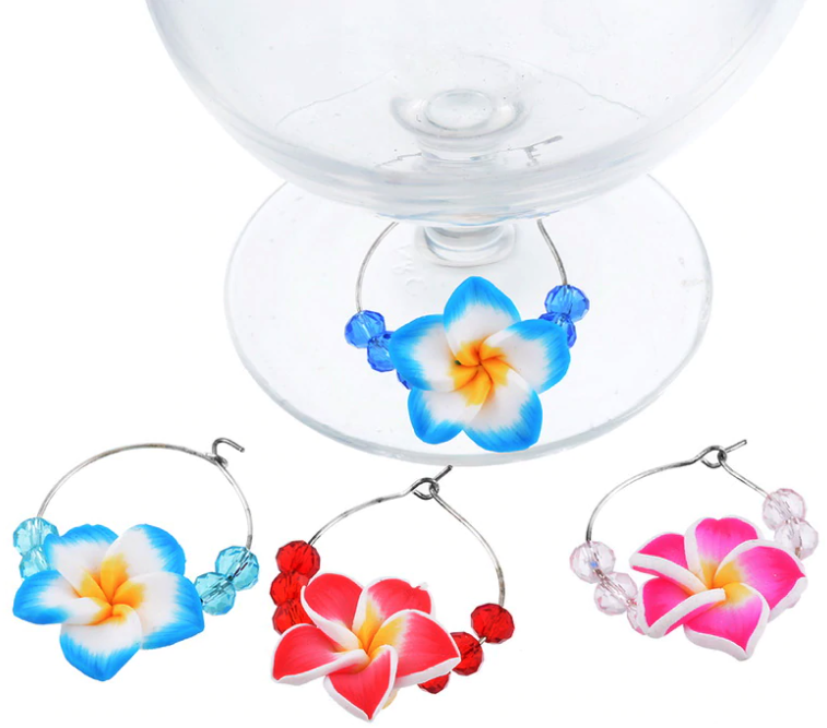 Different coloured frangipanis and beads threaded onto a circular piece of wire that hooks around wine glasses