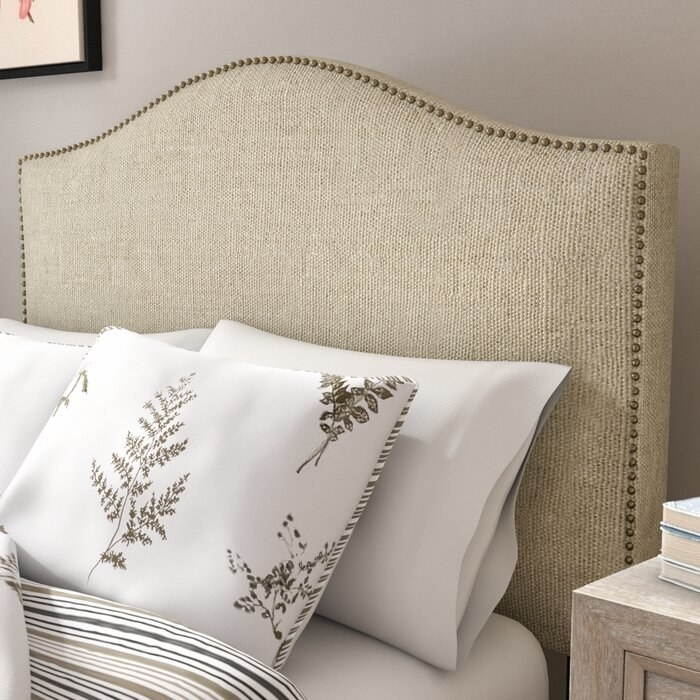 The headboard, which is upholstered in tan fabric, and has square edges, but a gentle arch at the board's peak