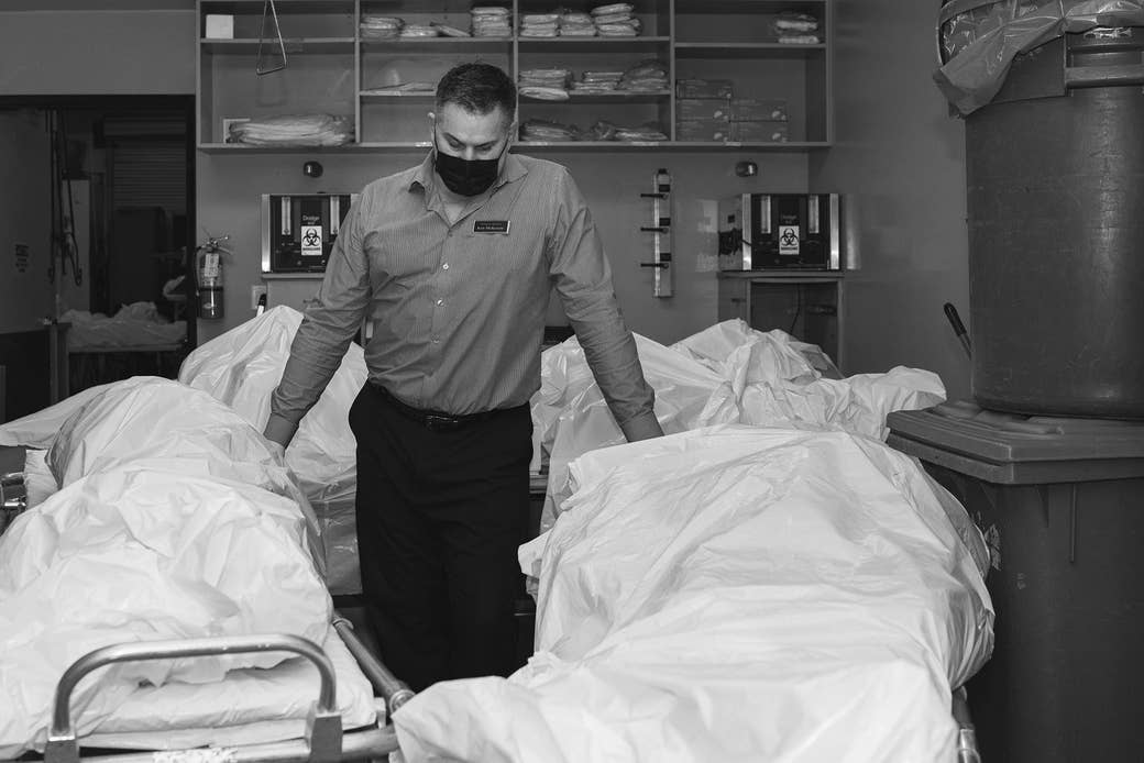 A man stands with a mask on surrounded by bodies in body bags